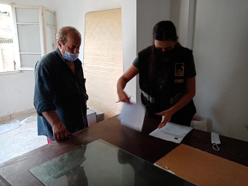 Assad and an IRC staff member review paperwork in his apartment.