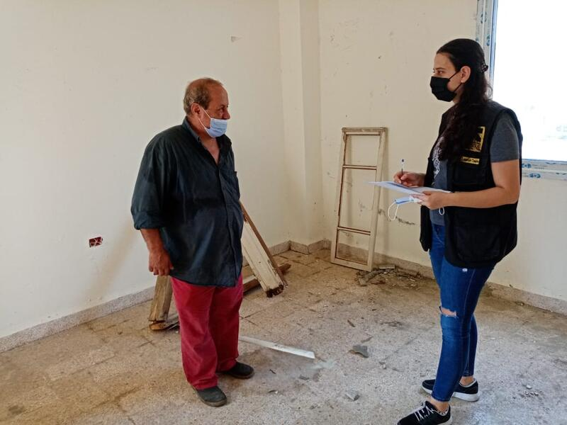 Assad speaks with an IRC staff member in his home amid repairs needed after the Beirut explosion.