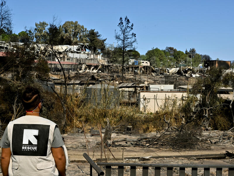 An IRC staff member views the remains of Moria refugee camp, destroyed by fire