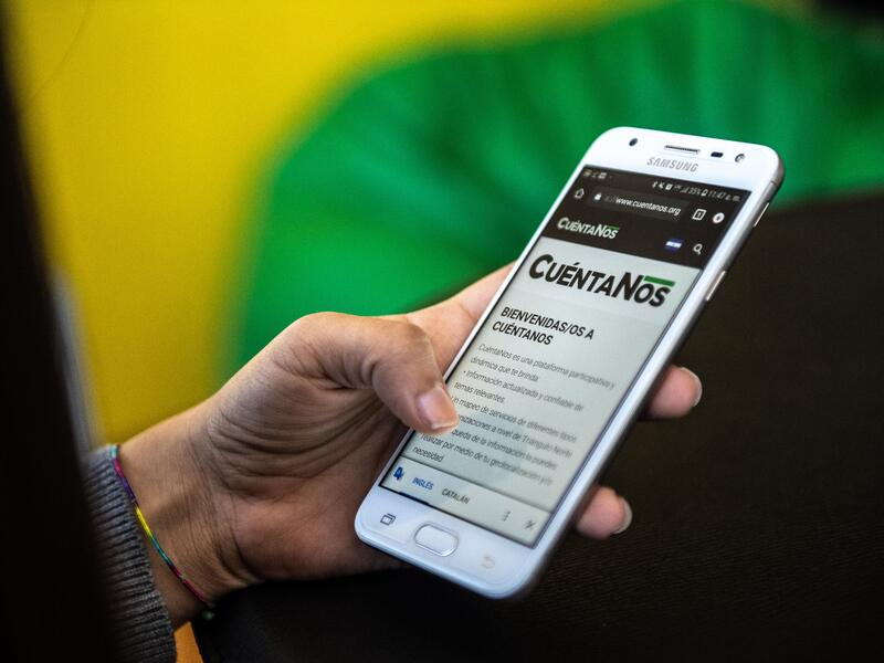 Close-up of a smartphone displaying the Cuentanos.org website in a women's hand