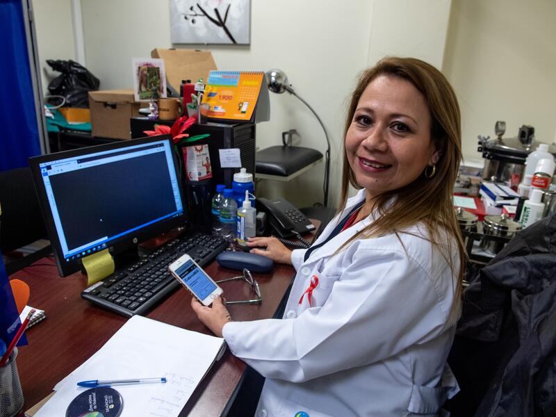 A doctor at her desk in San Salvador holds a phone displaying CuentaNos.org on its screen.