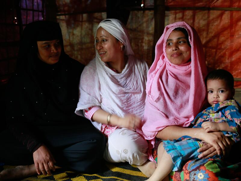 Rohingya activist and lawyer Razia Sultana sits with another Rohingya woman and her family in a refugee camp in Cox's Bazar, Bangladesh.