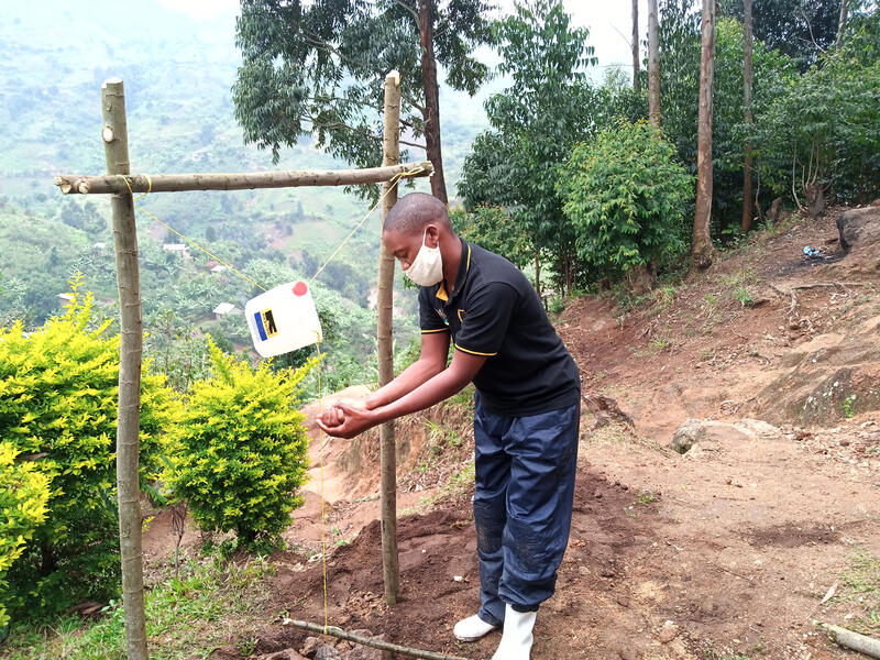 An IRC staff member in Uganda demonstrates the use of a handwashing station fashioned from sticks, rope, and a large plastic water jug.