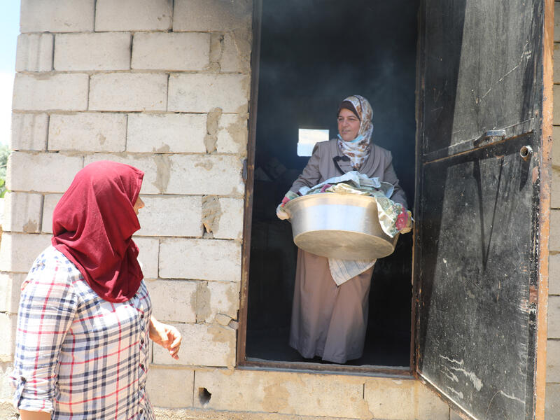 Syrian nurse and IRC community volunteer Mariam carries medical supplies out of a building while speaking with another woman outside the door