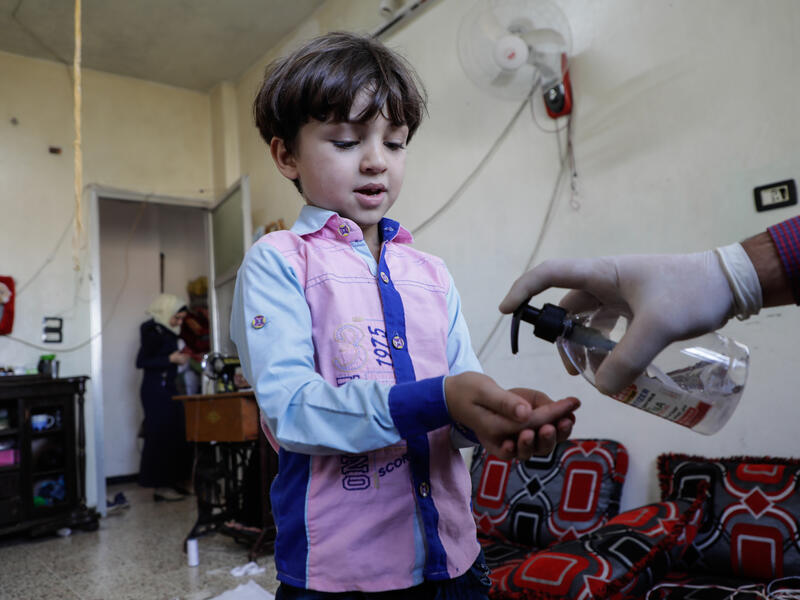 Five-year-old Murad holds his hands out as his father puts hand sanitizer on them inside their home in Syria during the COVID-19 pandemic.