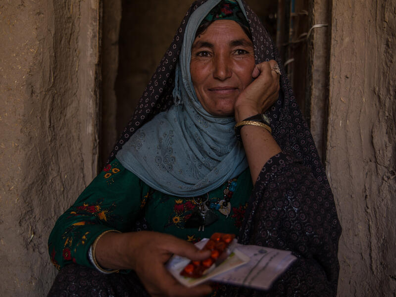An Afghan woman sits in a doorway holding medicine and prescriptions from the IRC as part of its Afghanistan crisis response.