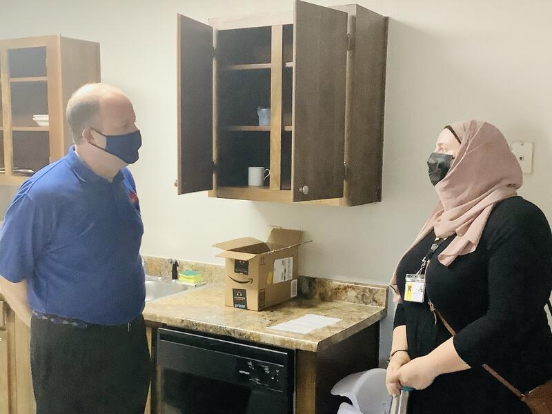 Colorado governor Jared Polis an an Afghan refugee woman speak in the kitchen of the woman's new apartment.