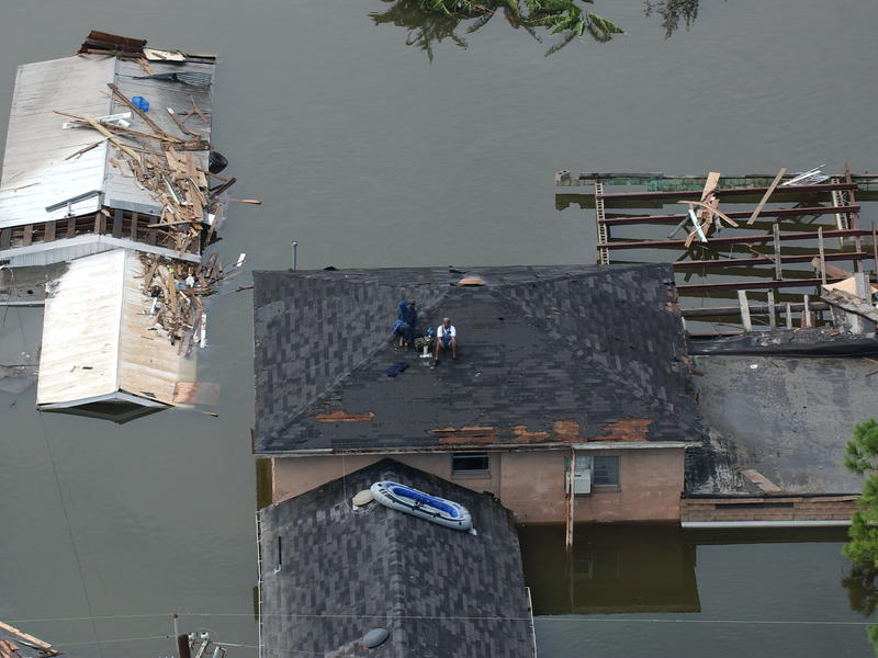 People sit on a roof in a flooded New Orleans neighborhood waiting to be rescued after Hurricane Katrin