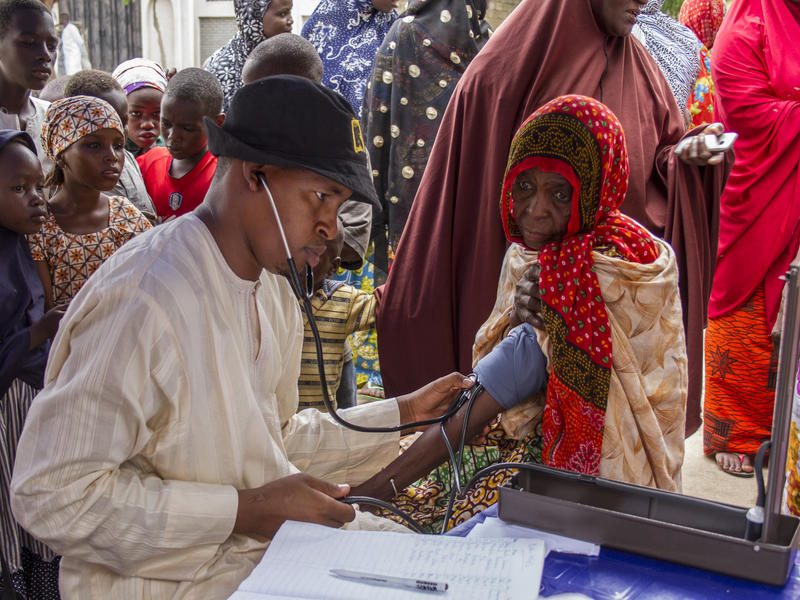 An IRC health worker checks the blood pressure of an elderly woman in an area where people have fled Boko Haram violence.