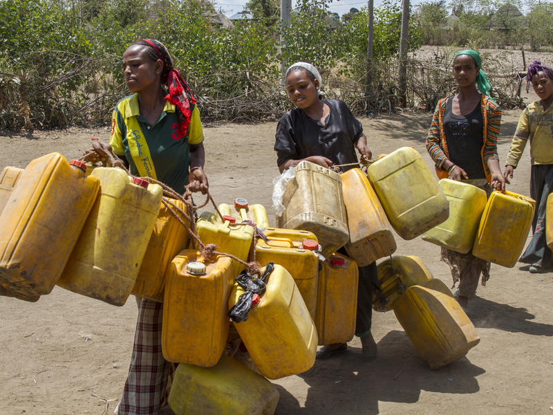 Women carry jerry cans