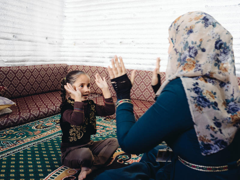 Five-year-old Hiba plays with her mother, Hisina in their home in Azraq camp in Jordan