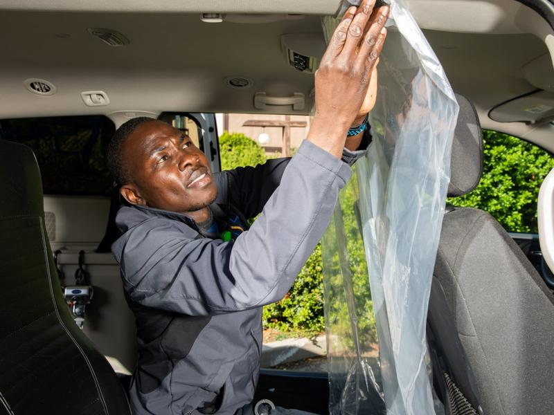 Jonathan puts up a sheet of plastic in one of his company vans as protection for his staff and clients.