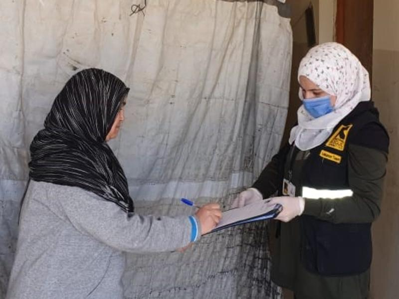 A woman in an IRC vest holds a clipboard while talking to an older woman and distributing cash assistance.