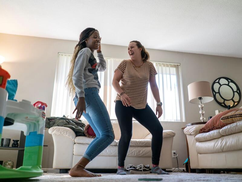 In the living room of Christelle's apartment, Christelle teaches Charlee dance moves as the two laugh. There are children's toys and two white couches also in the room.