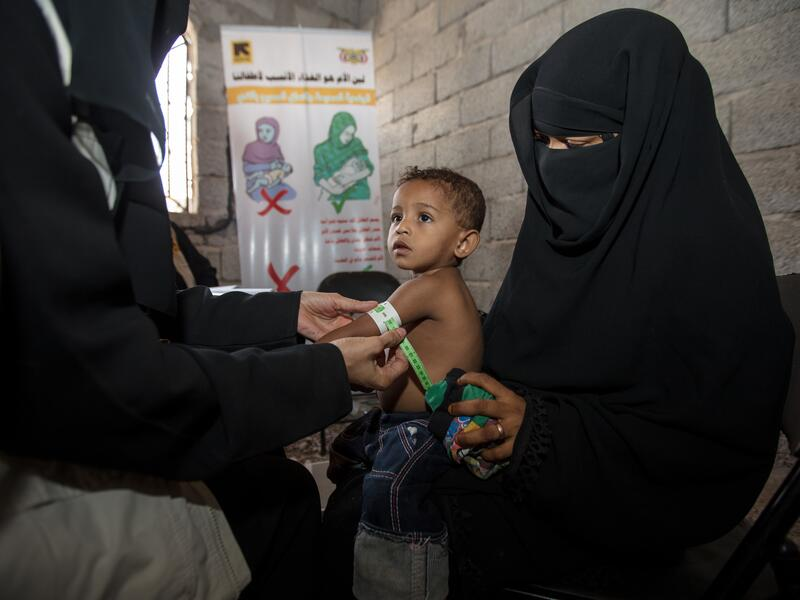 An IRC health worker in Yemen measures a toddler's upper arm for signs of malnutrition as he sits on his mother's lap.