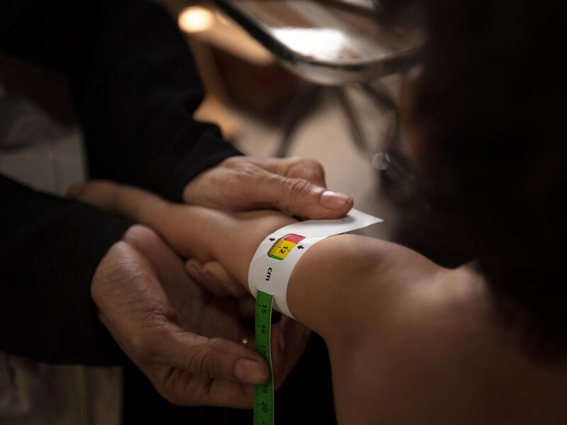 An IRC health worker measures a child's upper arm with MUAC tape to check for signs of acute malnutrition.