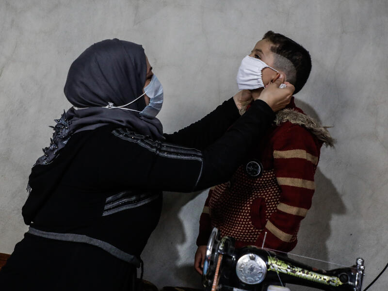 Um Abdo fits a mask on one of her young sons in northwestern Syria.