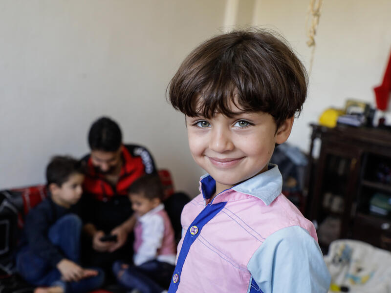 A smiling five-year-old Murad at home with his family in northwestern Syria.