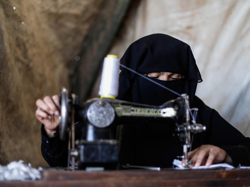 Wa'ad sews COVID-19 masks on a sewing machine in her makeshift shelter in northwestern Syria.
