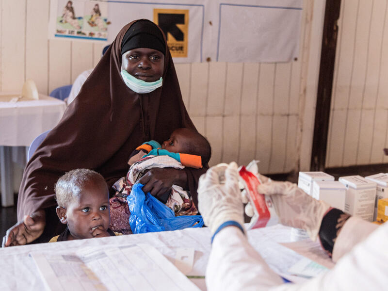 Amina sits at a table while holding a baby and putting her arm around her young son standing next to her. We can see a doctor's gloved hands holding therapeutic food.