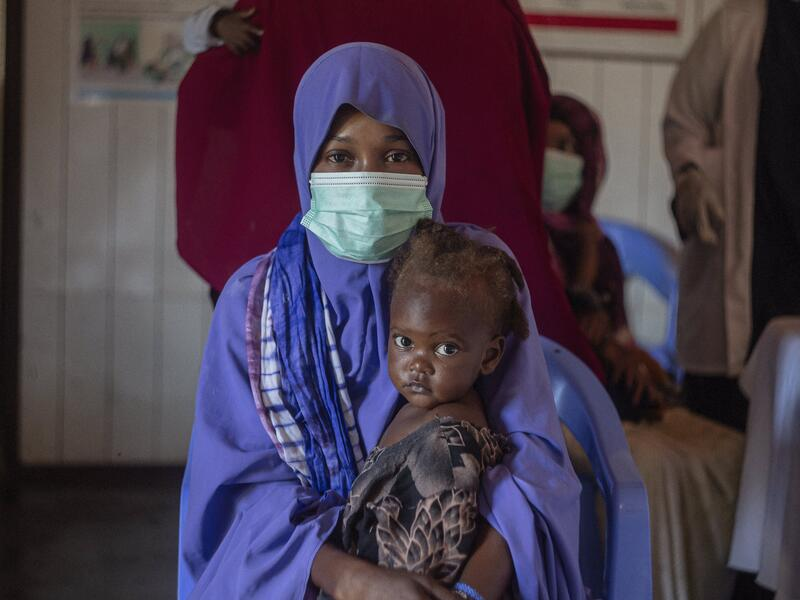 A woman holds her child as she receives treatment for malnutrition in the IRC clinic in Mogadishu.