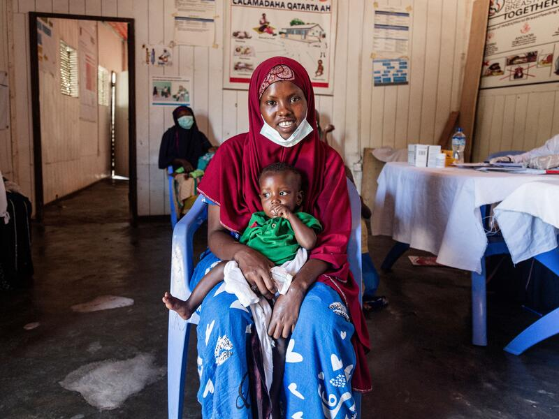 Farhiyo Abukar sits in a chair in the IRC clinic with her son on her lap.