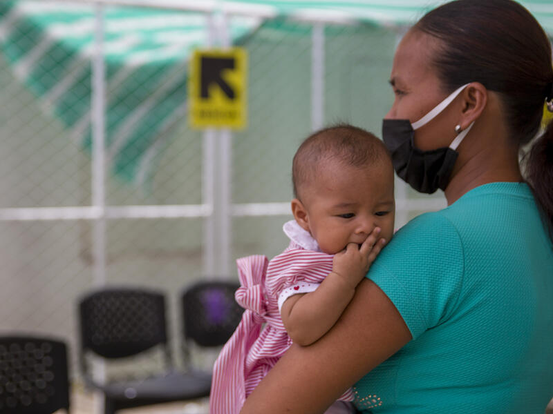 A mother wearing a face mask holds her baby daughter in the socially distanced waiting area of an IRC clinic on the Colombia-Venezuala border during the COVID-19 pandemic.