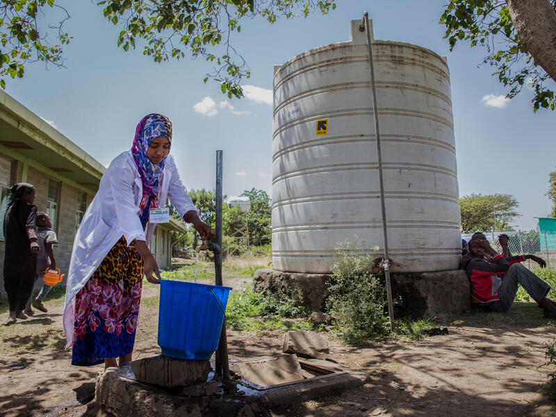 An IRC health worker in Ethiopia collects water in a large bucket