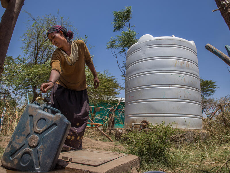 A woman fills a jerry can from a tap, part of a water system the IRC installed in Ethiopia.