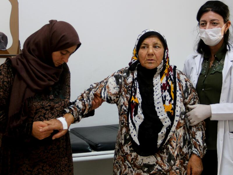 An elderly patient holds onto her daughter and the doctor as she leaves her consultation at a clinic run by the local health authorities with support from the IRC in Amuda, northeast Syria.
