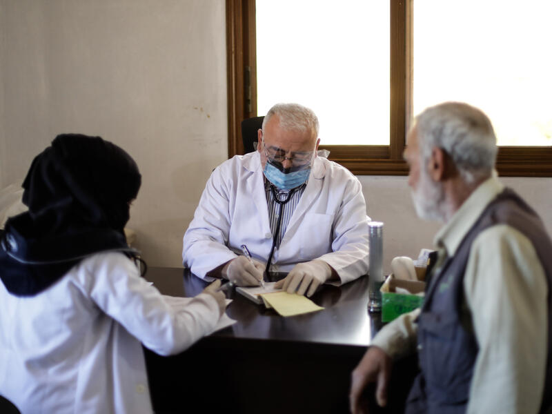A doctor sits at his desk at a clinic run by the IRC in Idlib. He wears a face mask to protect the staff and patient he is speaking with from COVID-19.