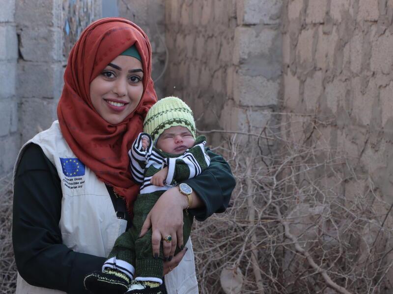 A smiling Dr. Bushra Al-Aghbari holds a sleeping infant boy in Yemen.