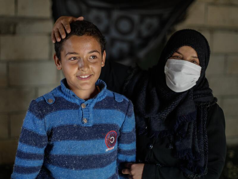 Tareq and his mother, Muna, in their home. She is holding his arm and has her hand affectionately resting on his head.