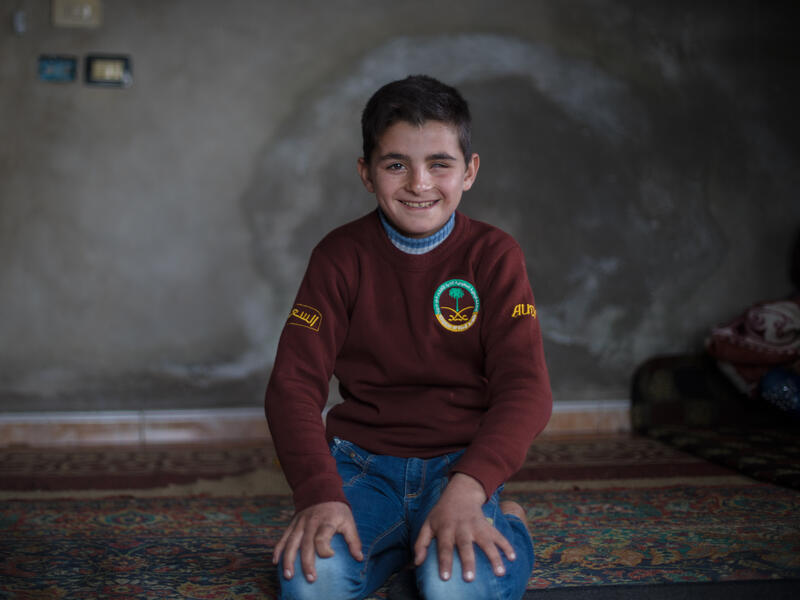Smiling, Ali sits on a rug on the floor of his home.