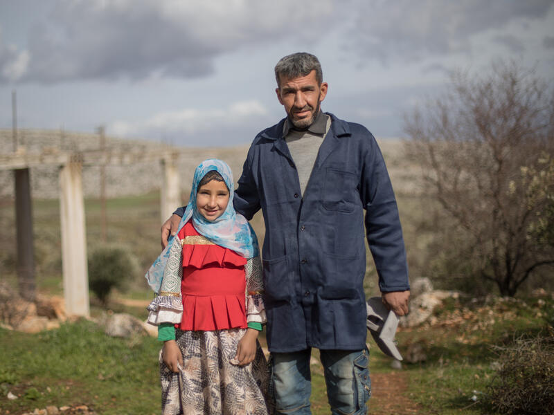 Sara and her father, Emad, stand outside. He has his arm around her and they are both looking at the camera.