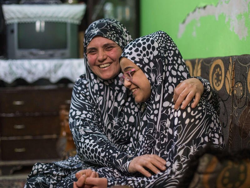 Salam and her mother, wearing matching outfits, sit in a couch and laugh together.