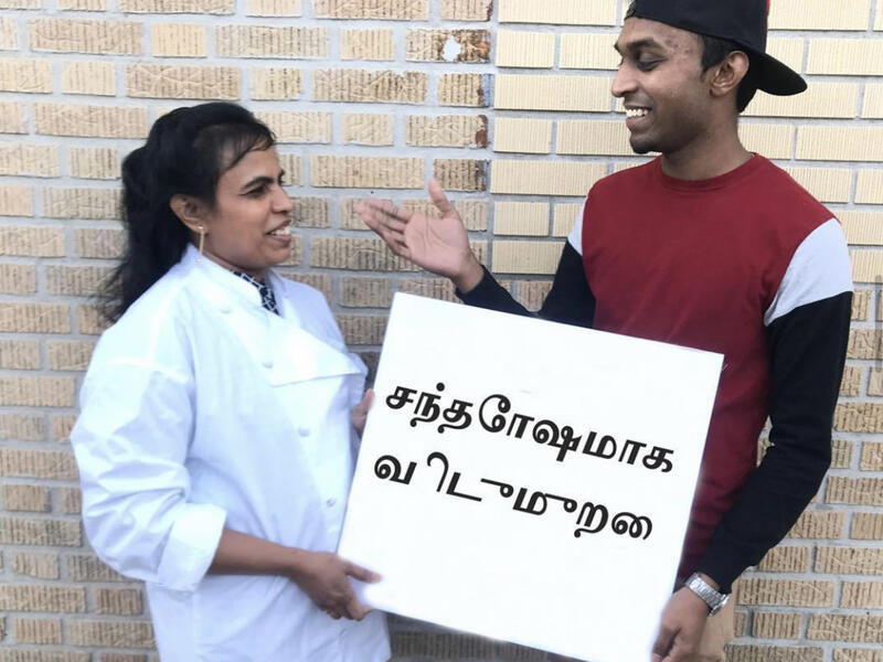 """Chef Shanthini and Sarujen, in front of a brick wall outside, look at each other and smile while holding a sign that says """"Happy Holidays"""" in Tamil."""