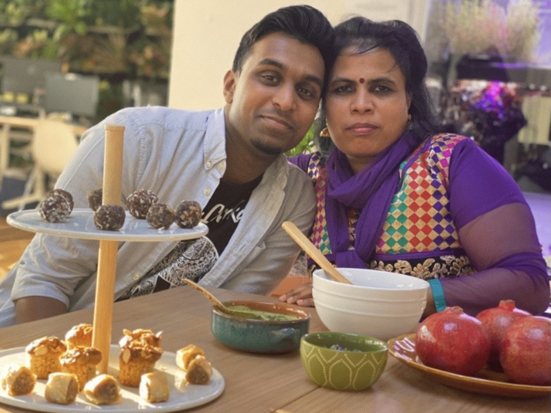 Sitting at a table with an array of food in front of them, Shanthini and Sarujen lean toward one another and look at the camera.