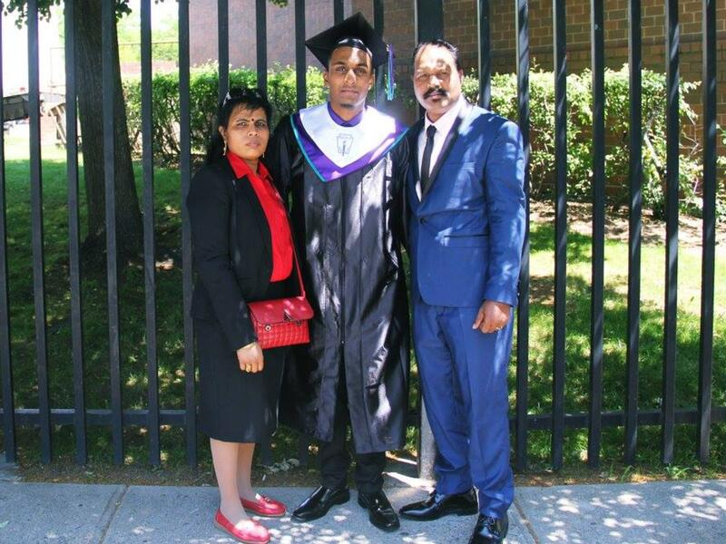 Wearing a graduation cap and gown, Sarujen stands in front of a fence with his parents on either side of him.