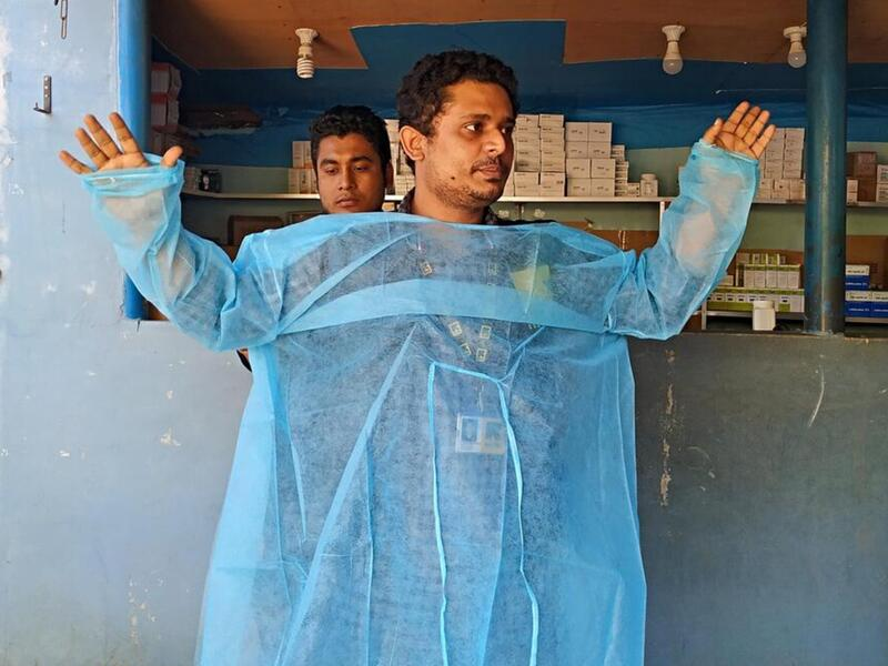 Dr, Mahmudul Hossain stands in front of a group of health care workers and volunteers and demonstrates how to correctly put on a medical gown.
