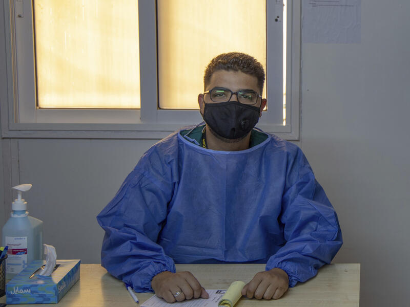 Dr. Abedalhaleem Albalasmeh, wearing a mask and a medical gown, sits behind a desk at an IRC clinic in Jordan.
