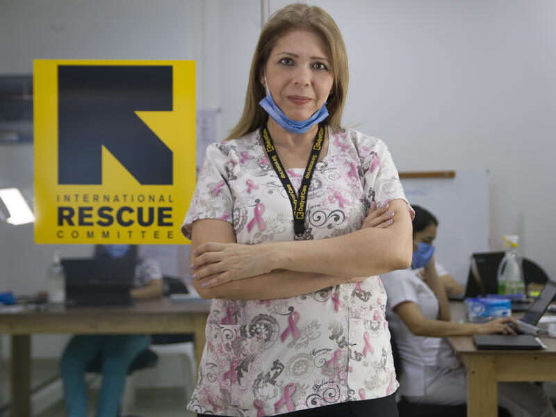 Dr. Edna Patricia Gomez stands in front of an IRC logo in a clinic wearing her medical scrubs and a mask around her chin.