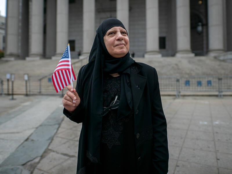 Maha al-Obaidi stands in front of the federal court house while holding a flag