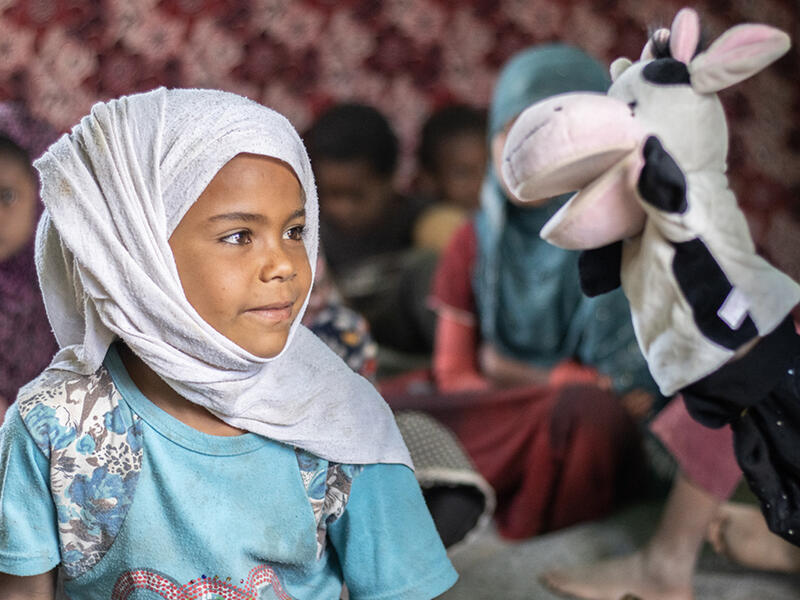 In Al-Manshar camp, a litle girl sits and looks at a cow puppet that a volunteer is using to teach her about COVID-19 prevention.