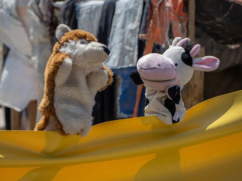 """Using a yellow tarp as their """"stage,"""" a cow and fox puppet have a """"conversation"""" during a puppet show on COVID-19 prevention"""