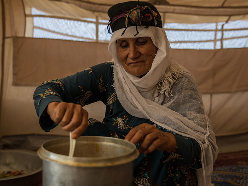 An Afghan woman stirs food in a pot while sitting in a tent in a refugee camp