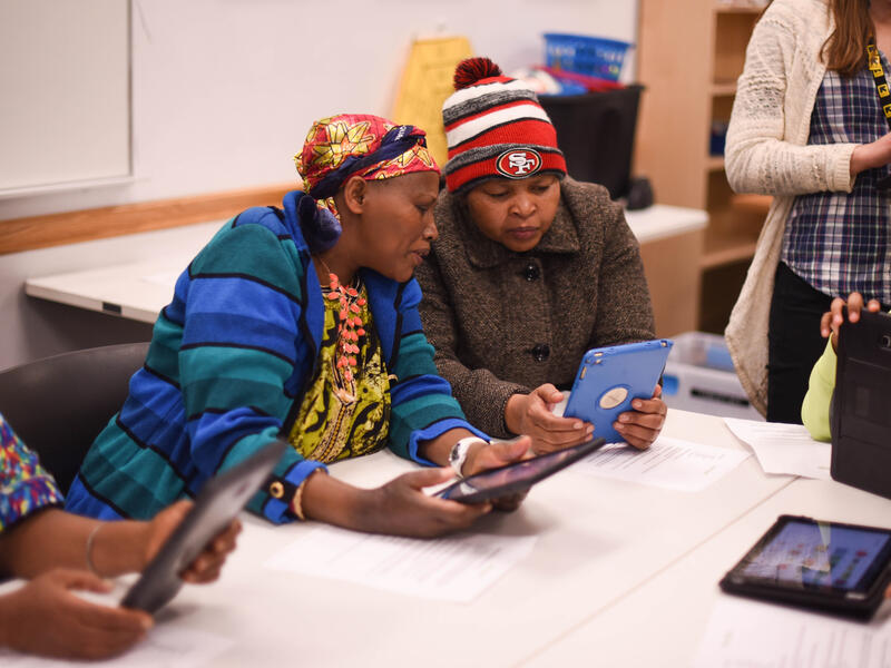 Participants in a tablet workshop by the IRC in Salt Lake City's digital inclusion program look at their tablets