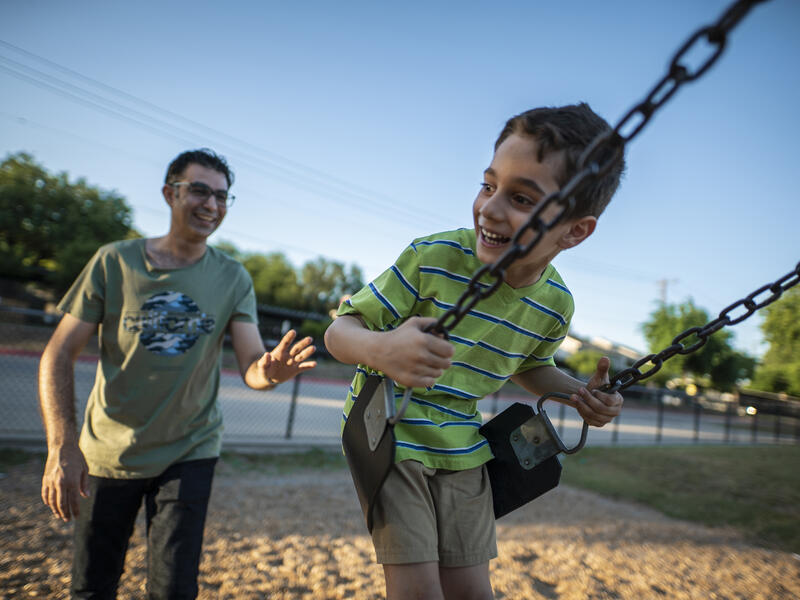 Iraqi refugee Junaid pushes his son on a swing in a park in Dallas, Texas