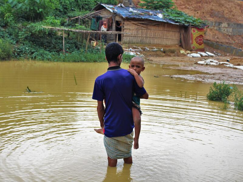 Nurul Hauqe, 50, carrying his two-year-old son, wades through nearly knee-high monsoon floodwater in Cox's Bazar, Bangladesh after escaping violnmar.ence in Mya