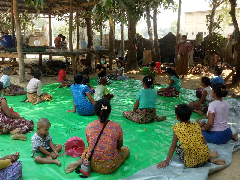 People listen to an IRC health worker provide health information. They are sitting outdoors socially distanced on a mat as a COVID-19 precaution.